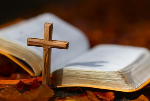 An open Bible placed alongside a Christian cross