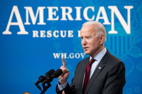 """President Biden speaking behind a microphone and in front of a sign that says """"American Rescue Plan."""""""