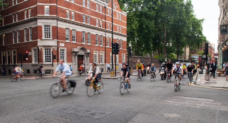 Commuter cyclists set off from a green light at a busy road junction in Central London