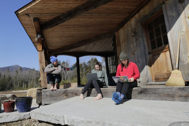 Three people sitting on a porch trying to connect their laptops to internet.