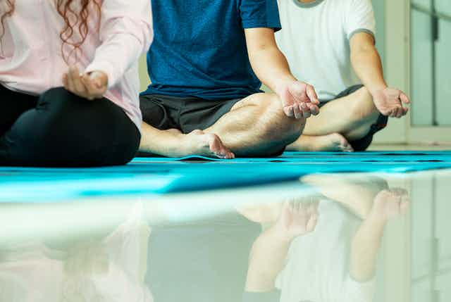 Three people sit on mats with their legs crossed in a meditation pose.