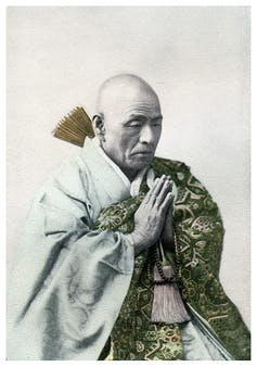 A vintage photograph of a Buddhist priest in repose.