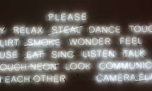 A neon sign of floating words, some of which say Please dance touch feel wonder