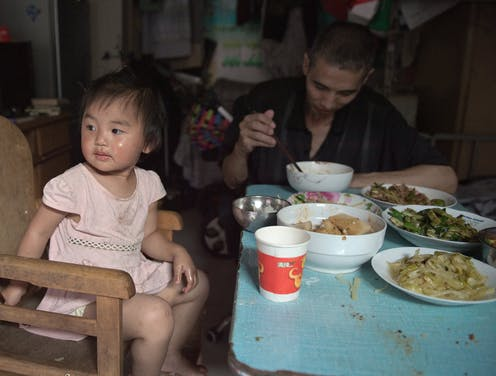 A Chinese toddler eats a big meal with her father in a cramped home.