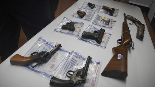 A collection of illegal guns including eight pistols and a rifle is displayed on a table during a gun buyback event in Brooklyn, New York.