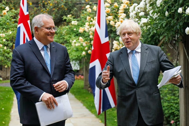 Scott Morrison and Boris Johnson in a garden with their national flags