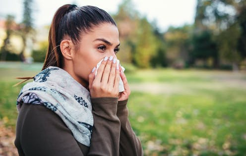 Woman who looks otherwise healthy blows her nose.