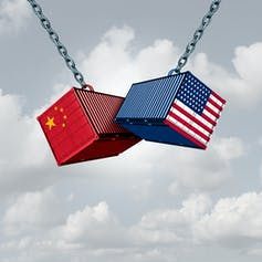 Shipping containers with Chinese and American flags banging against each other.