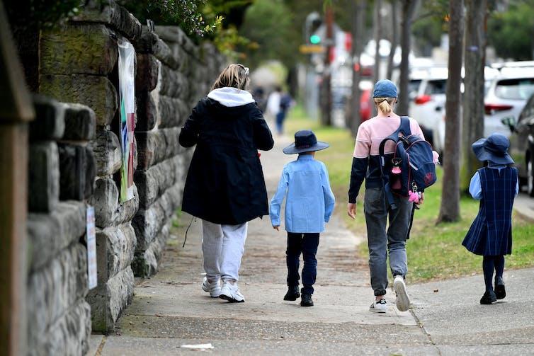 School children walk with parents down a street in Sydney.
