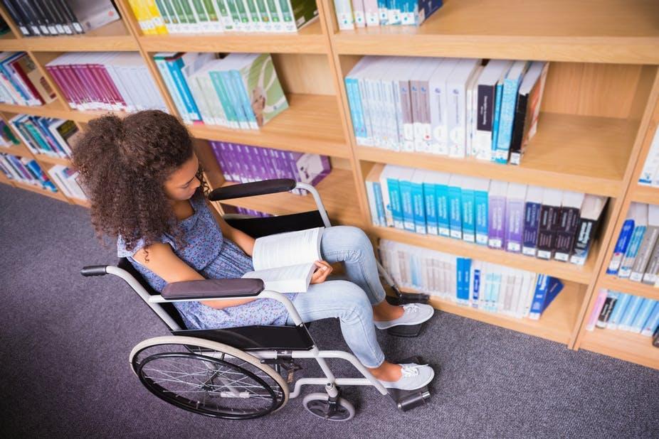 A young woman sitting on a wheelchair in a library and reading a book.