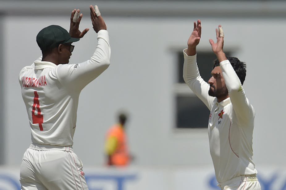Two men in white cricket clothes, hands held aloft as they approach one another for high fives.