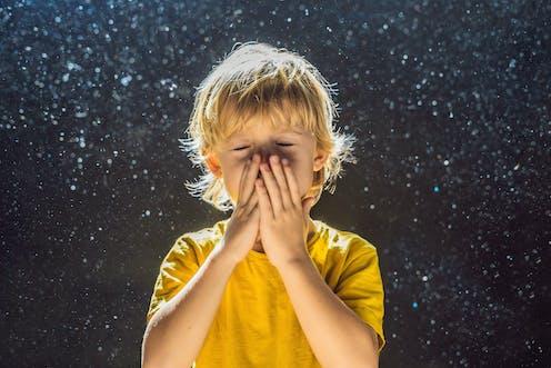 Un niño se echa las manos a la nariz para estornudar.