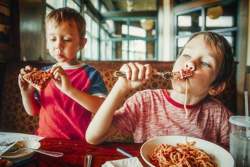 Dos niños comen pasta y pizza.