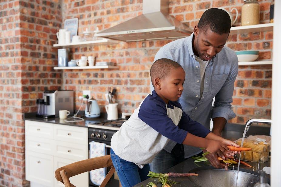 Boy helping man prepare food in kitchen
