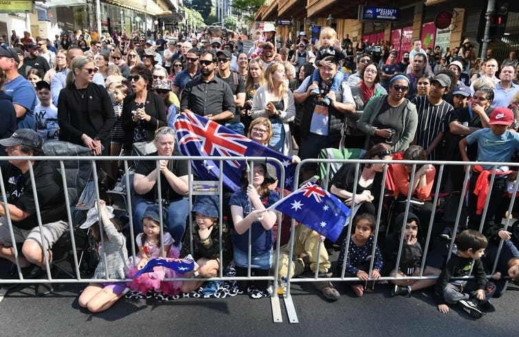 Crowds wait for an Anzac Day march.