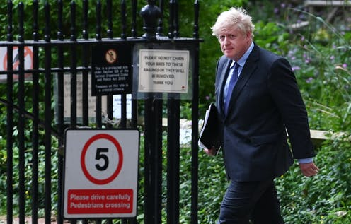 Prime minister Boris Johnson walks outside, carrying a folder of papers and looking solemn