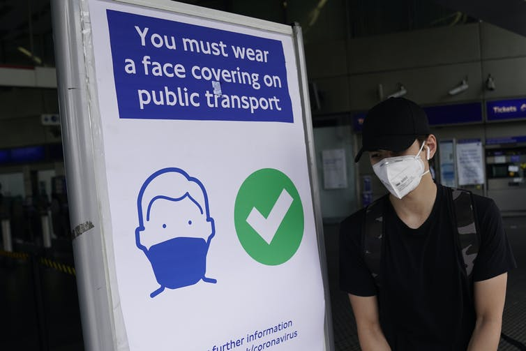 A commuter in a face mask walks by a sign that says