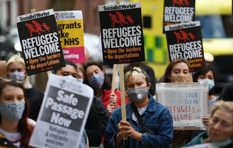 Protesters against the UK's asylum policy wearing facemasks and holding placards demanding safe passage for refugees.