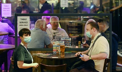 People wearing masks in a pub offering table service