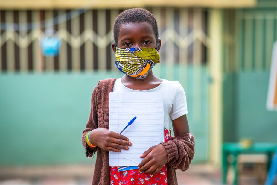 Child wit ha mask standing holding a notepad and a pen.