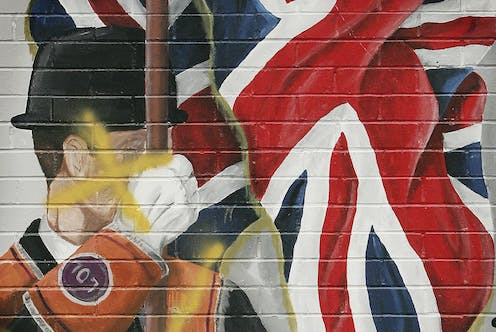 A defaced mural showing a member of the Orange Order is seen in Loyalist area of East Belfast.