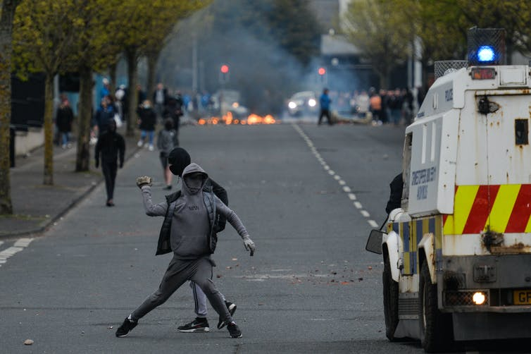 Loyalists throw a rock at police vehicles during unrest in Northern Ireland in April, 2021