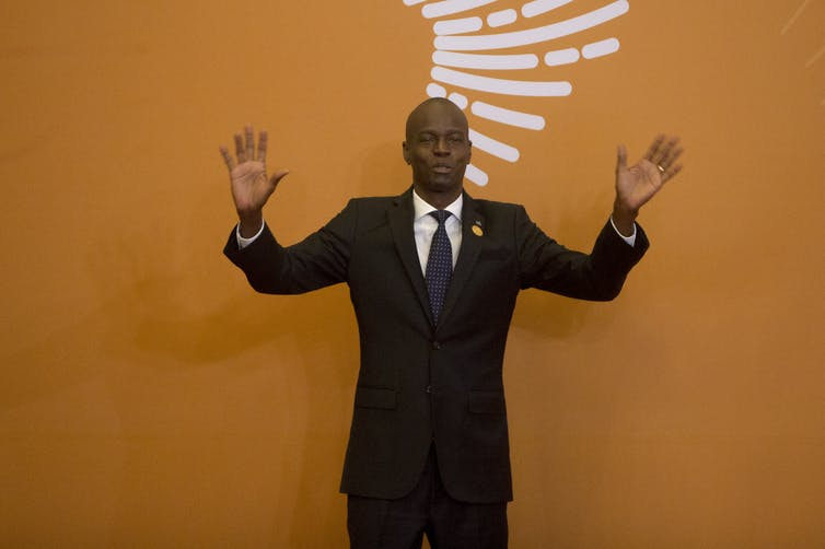 President Moïse in a black suit, raising his hands in front of an orange backdrop.