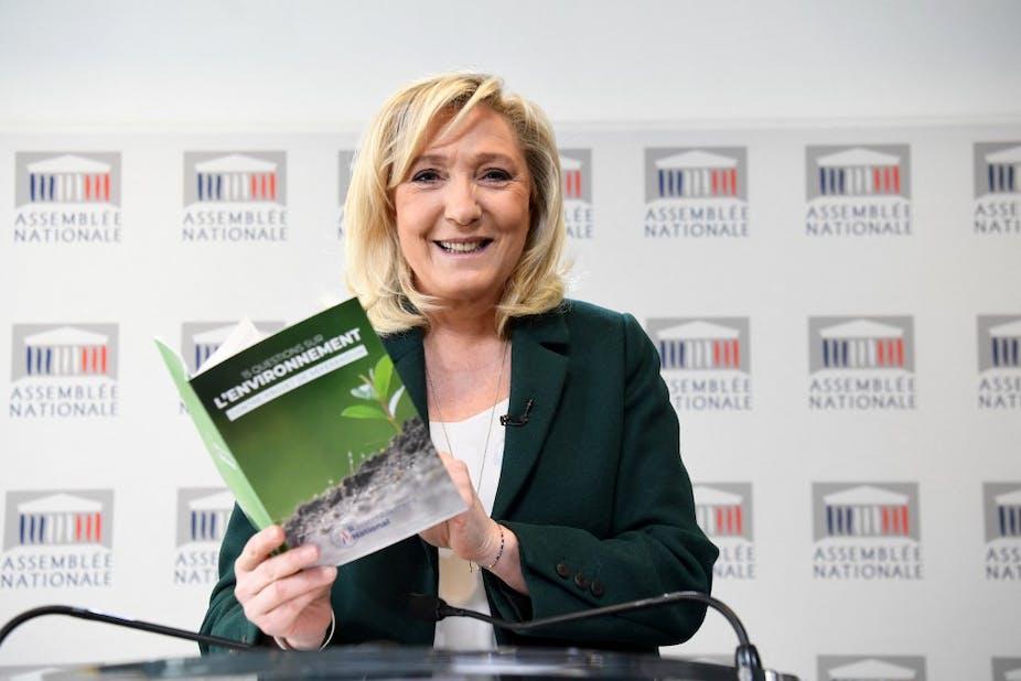 Marine Le Pen tient  à la main une brochure sur sa contre-proposition au projet d'amendement constitutionnel incluant le devoir de lutter contre le changement climatique, le 9 mars 2021.