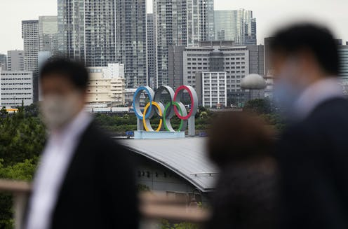People in masks walk in the foreground as the Olympic rings are on a building in the background