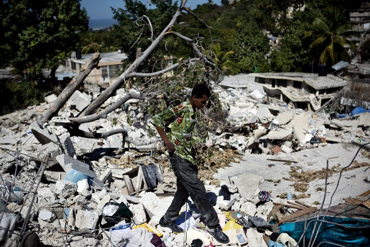 A man walks over the remains of several homes where bodies of earthquake victims had yet to be pulled from the rubble.