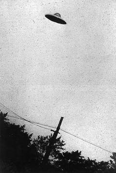 A grainy black and white photo showing a flying saucer in the sky.