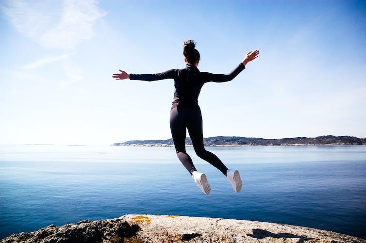 Une femme semble léviter près d'une falaise