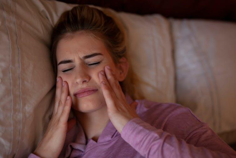 Une jeune femme dans son lit se tient les joues