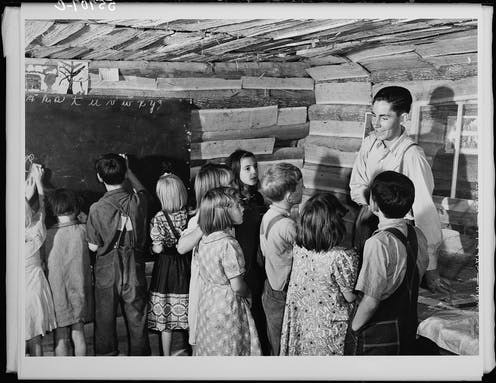A teacher talking with students in a ramshackle one-room schoolhouse in 1940.