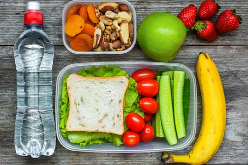 Lunchbox with cucumbers, tomatoes and a sandwich. A bottle of water and some fruit next to it and a separate lunch box with nuts and dried apricots.
