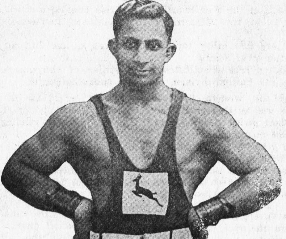 Black and white photograph of well muscled man with arms akimbo, wearing wrist supports and athletic vest with Springbok emblem