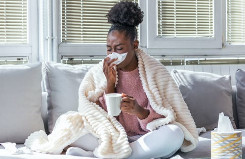 A woman with flu blowing her nose