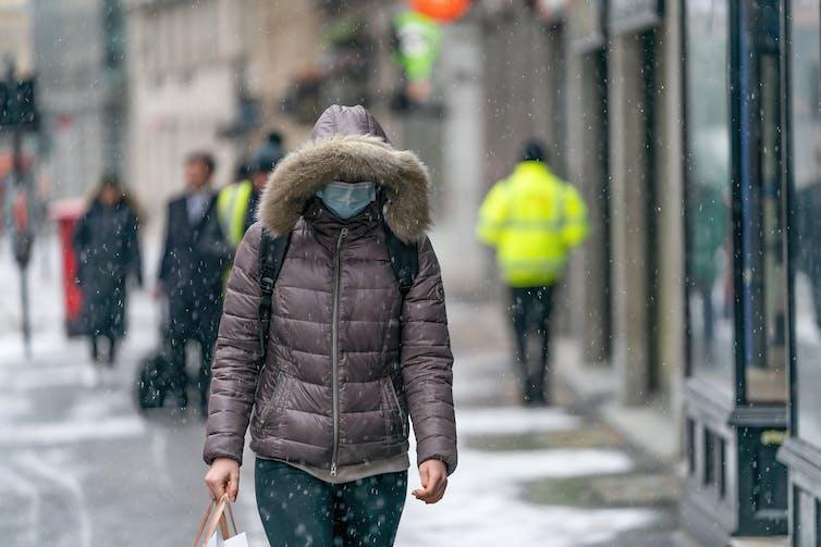 A woman walking outside in winter in a mask