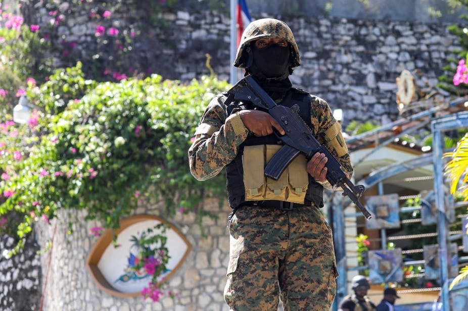 Militaire haïtien en tenue de camouflage tenant une arme