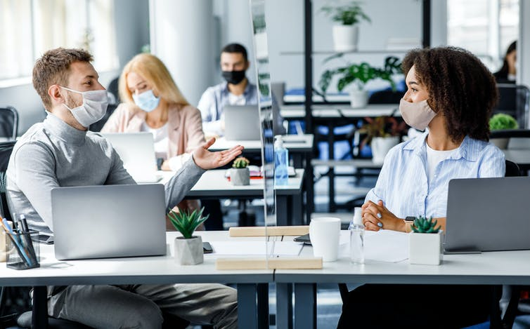 Two office workers wearing masks and sitting at their desks chatting.