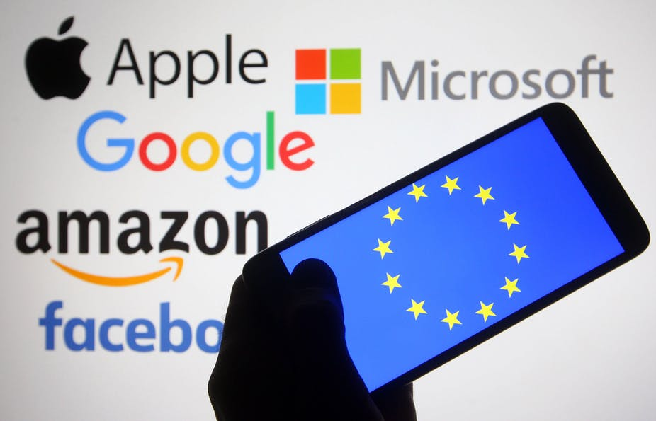 Silhouette of hand holding smartphone with EU logo with logos of big US tech companies in the background