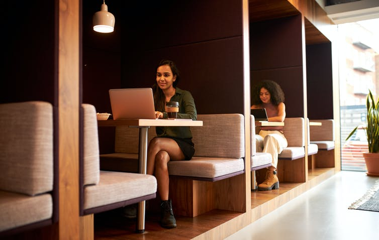 people working in office with breakout spaces.
