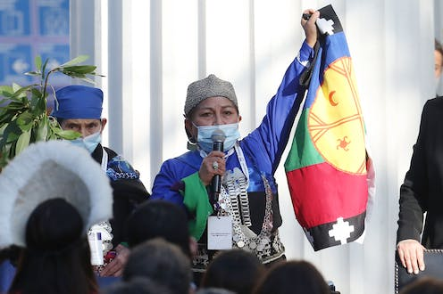 Indigenous Chilean academic Elisa Loncon, wearing a face mask and holding up a Chilean flag, makes a speech in Santiago, CHile, July 4 2021.