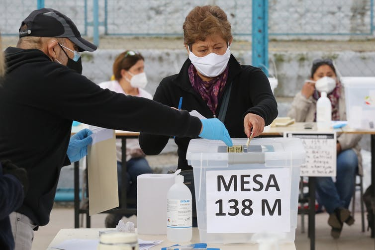 A Chilean man wearing a COVID mask casts his vote while an election monitor looks on.