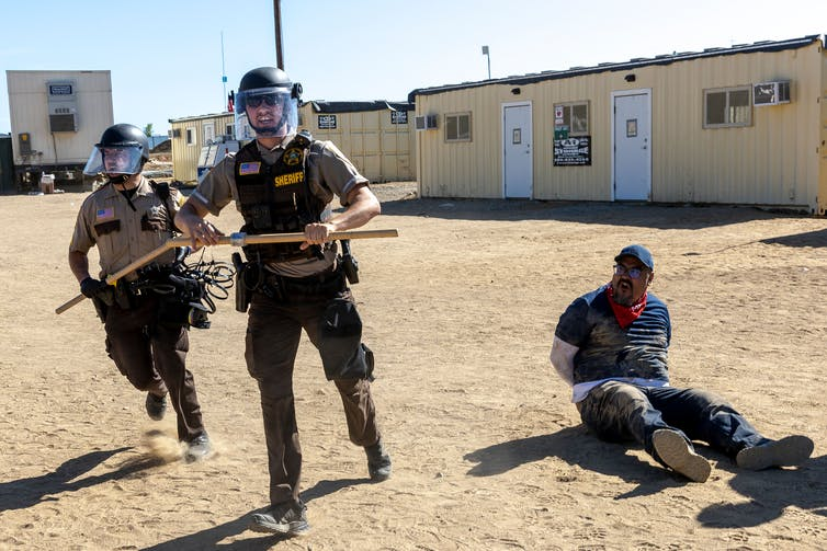 Two police in riot gear run while handcuffed man sits on ground
