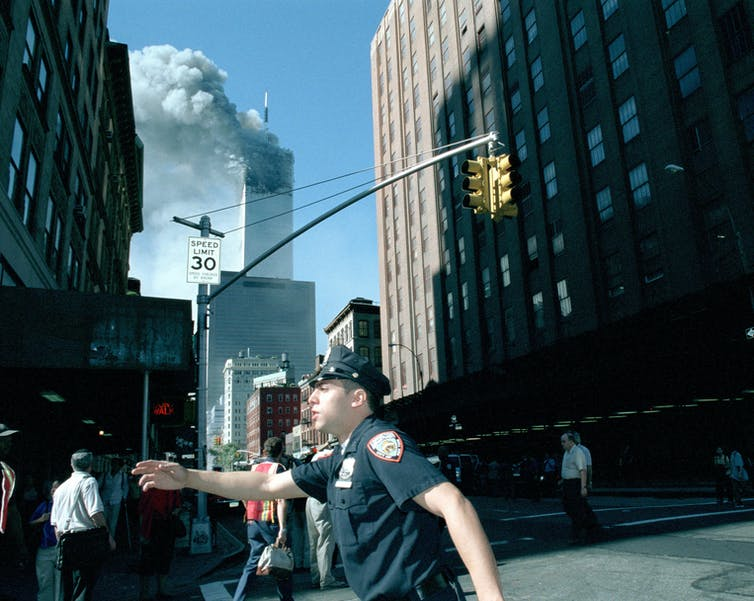 Police officer directing traffic in New York while World Trade Center burns after two planes crash into the twin towers