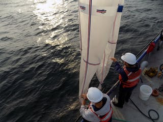 Dos personas arrojan al agua redes cónicas de un barco de investigación.