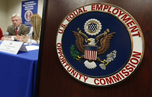 The U.S. Equal Employment Opportunity Commission seal is displayed in the foreground as a man and a woman chat at a table with a blue cloth draped over it.