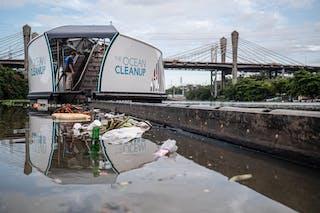 Gran barcaza con cinta transportadora que saca los desechos plásticos del río.