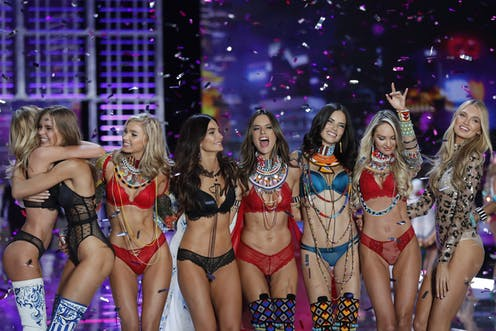 8 victoria's secret models stand side by side at the Victoria's Secret fashion show.